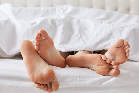 Female`s and male`s bare feet have rest under white blanket, recreat together, feels relaxation. Unrecognizable family couple sleep in comfortable bed. Bed time and good rest concept Stok Fotoğraf