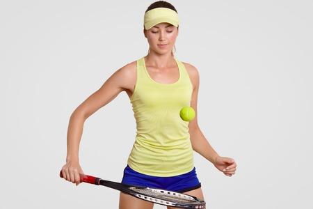 Aantrekkelijke jonge vrouwelijke professionele tennisspeelster hit tennisbal met racket, treinen in de sportschool, hoofdband, korte broek en poloshirt draagt, heeft geconcentreerde uitdrukking, geïsoleerd op witte achtergrond.