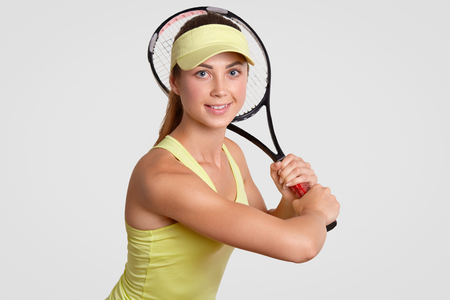 I am ready to play! Beautiful healthy active woman in court cap, casual t shirt, holds tennis racquet, looks positively directly at camera, isolated over white background. People, hobby concept