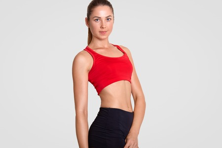 Shot of pleasant looking sporty woman has perfect figure, dressed in casual red top and black shorts, motivates you to go in for sport, isolated over white background. Healthy lifestyle concept Reklamní fotografie