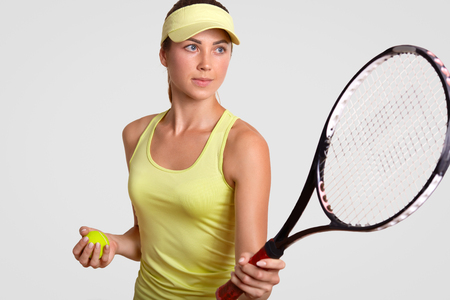 Horizontal portrait of pretty professional female tennis player holds racquet, ready to make favourite shot, holds ball, poses against white background, dressed in sportsclothes. Healthy lifestyle