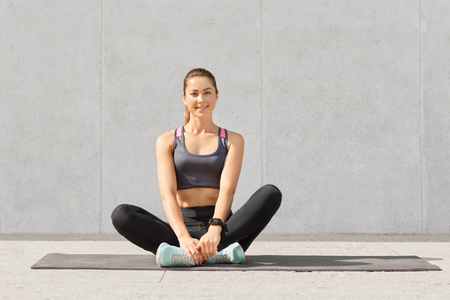 Pretty woman goes in for sport regularly, dressed in sportswear, sits crossed legs on mat in gym, has rest after yoga exercises, poses against grey background, has healthy lifestyle. Sport concept Stock Photo