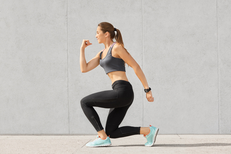 Indoor shot of self determined woman with pony tail, stands on one knee, warms up before cardio training, wears tanktop, leggings, sneakes, goes in for sport regularly, isolated over grey background Stock Photo