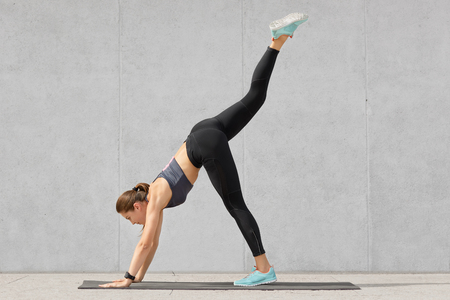 View of young sporty girl has elastic body, stands on hands, raises legs, does stretching exercises, dressed in comfortable black leggings, tanktop, poses on fitness mat against grey background Stock Photo