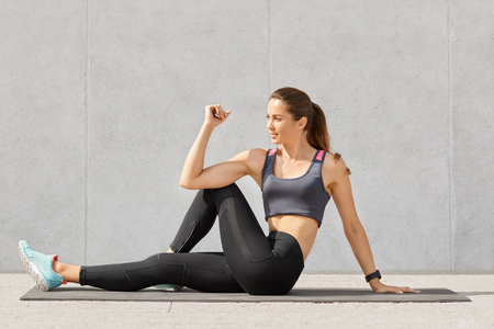 Sporty fitness trainer in casual top and leggings, makes stretching exerices for legs, sits on floor on mat, poses against grey background. Active sportswoman shows her acrobatics skills indoor