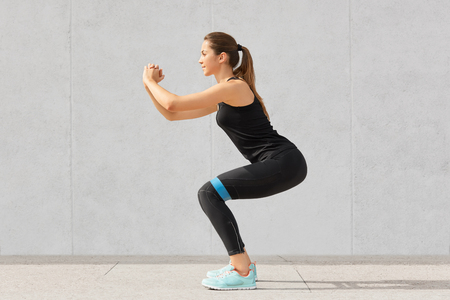 Strong sporty Caucasian woman has exercises with rubber resistance band, trains legs, works on muscles, dressed in t shirt and leggings, stands indoor against grey background in fitness studio