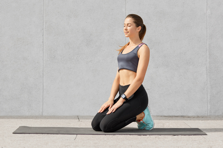 Concentrated young sporty European fitness woman sits on mat, tries to take break after stretching or practicing yoga, keeps eyes closed, poses against grey background. Healthy lifestyle concept. Stock Photo