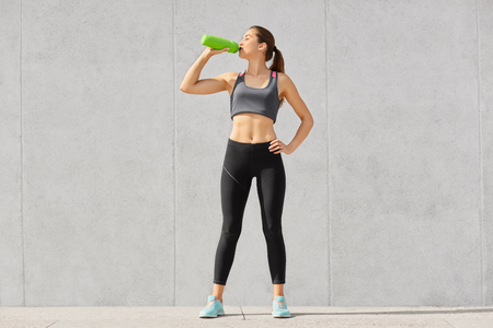 Thirsty slim athletic woman wants to drink after active training, holds green bottle, keeps hand on waist, dressed in sportswear, isolated over grey concrete wall. People and weariness concept.