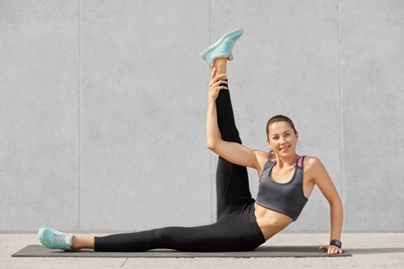 Photo of attractive woman does abdominal exercises, raises leg, poses on fitness mat indoor, has satisfied expression, models against grey concrete wall. People, gymnastics, lifestyle concept Stock Photo