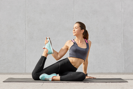 People and active exercises concept. Beautiful European young woman with darkhair, dressed in sportswear, raises legs for stretching before aerobics, poses on fitness mat, isolated on grey wall Stock Photo