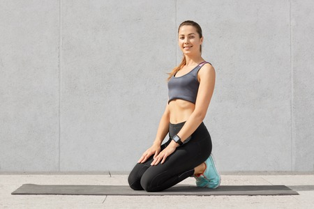 Satisfied smiling woman being in good mod after doing crunches on fitness mat, stands on knees, dressed in sportswear, has healthy fit body, fresh skin, goes in for sport regularly. Training concept