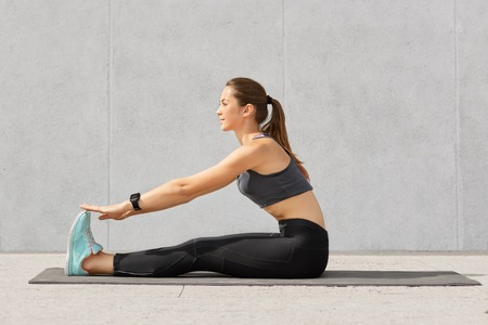 Photo of motivated girl does stretching workout or acrobatics exercises on fitness mat, recieves yoga lesson, has dark hair combed in pony tail, dressed in sportswear, poses against grey background. Stock Photo