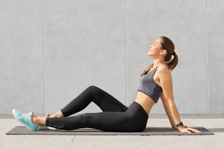 People, sport and relaxation concept. Relaxed fitness woman with perfect figure sits on exercise mat, keeps eyes closed, dreams about something after having morning workout or yoga practice. Stock Photo