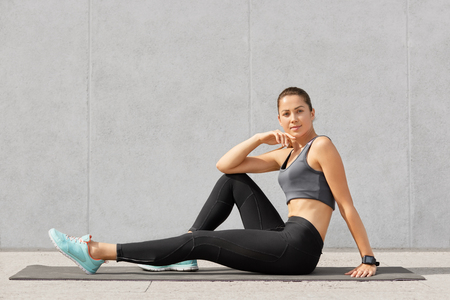Hoizontal shot of sporty girl rests after acrobatics exercises, sits on exercise mat, looks directly at camera, wears tanktop, black leggings and sneakers, poses over grey concrete wall alone Stock Photo
