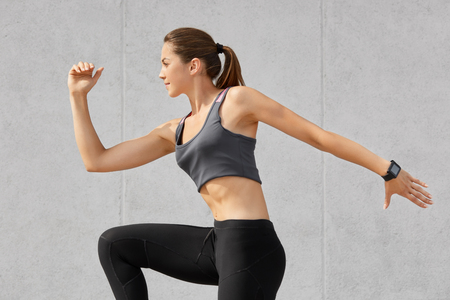 Active bodybuilder girl being photographed in motion, has dark pony tail, does stretching exercises dressed in casual clothes, poses against grey background. Gymnast female has fitness goals Stock Photo