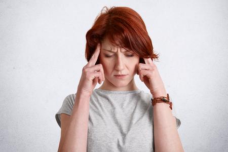 Nachdenkliches rothaariges konzentriertes Weibchen hält Finger an Schläfen, versucht sich an etwas zu erinnern, konzentriert sich nach unten, trägt Freizeitkleidung, isoliert über weißem Hintergrund. Menschen und Gedanken