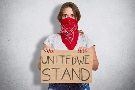 Attractive serious young woman holds plate, wears casual clothes and red stylish bandana on face, belongs to feminist move, defenses females, isolated over white background Standard-Bild