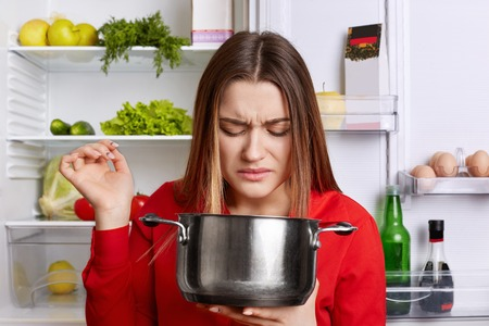Pretty woman holds saucepan, feels unpleasant stink as there is spoiled dish, wears red blouse, stands near opened fridge, going to cook fresh dish.
