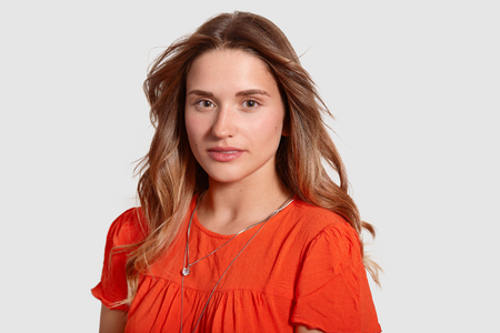 Headshot of gorgeous lovely young female with healthy skin, wavy luxurious hair, dressed in orange sun dress, looks directly at camera, isolated over white background.