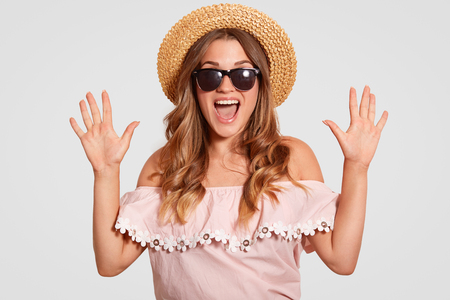 Photo of amazed attractive woman with overjoyed expression, reacts on something wonderful, keeps hands raised, exclaims with happiness, dressed in fashionable clothes, isolated on white wall
