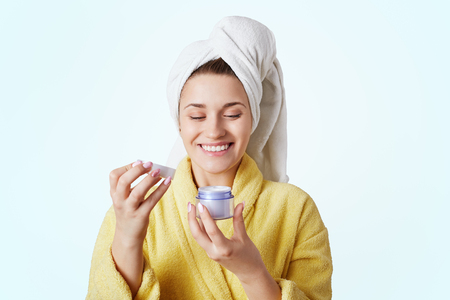 People, spa, beauty, cosmetics, skin care concept. Smiling female in towel and bathrobe, looks happily at new cream for face, glad to buy new cosmetic product, care about skin and her appearance