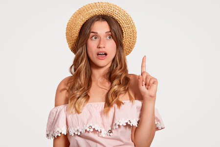 Horizontal shot of surprised young European woman with pleasant appearance, long hair, wears summer hat, blouse, points with index finger upwards, stands against white background.