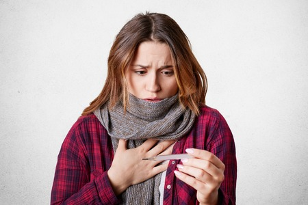 Sick beautiful woman looks at thermometer, has high temperature, flu, wears warm scarf on neck as has sore throat, shocked, isolated over white background.