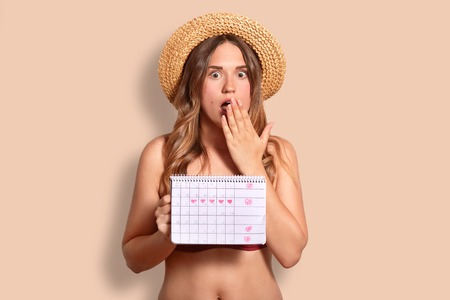 Shocked European female covers mouth, being speechless, holds period calendar, wears summer hat and bikini, controls her periods, isolated over studio background. Archivio Fotografico