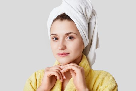Headshot of beautiful lovely young female has cared healthy skin, wears towel on head, dressed in yellow bathrobe, looks directly into camera, isolated over white background.