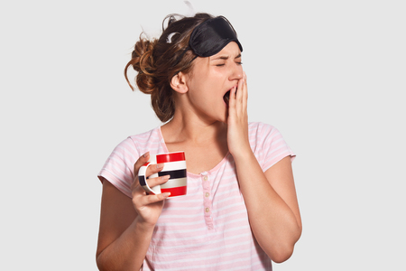 Indoor shot of beautiful female wants sleep badly, yawns and closes mouth with hand, wears blindfold and casual t shirt, holds mug with refreshing beverage, stands against white background
