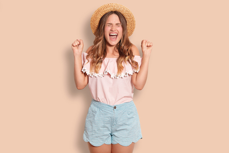 Horizontal shot of cheerful young European female clenches fists, exclaims with happiness, closes eyes, wears summer hat, blouse and shorts, poses against studio background.