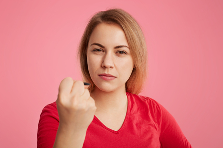 Serious angry woman puts up fist as tries to warn you, dressed in red sweater, isolated over pink background. Pleasant looking female shows fist, being strict and aggressive, tries to show her power