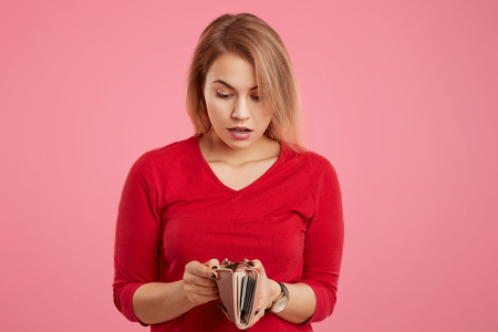 Surprised female model being short of money, looks with shocked expression in wallet, has not enough money for paying for her purchase, isolated over pink background. People and financial problems Banco de Imagens