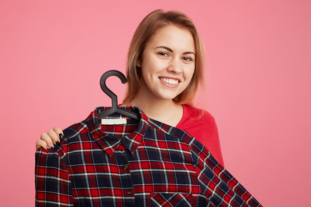 Positive cheerful young woman advertises fashionable checkered shirt on hangers, proposes to buy it with low price, suggests discount, isolated over pink background. People and shopping concept