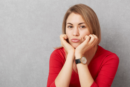 Photo of sad pretty woman leans at hands, pouts lips, wears fashionable watch and red sweater, looks with upset expression into camera, isolated over grey background. Facial expressions concept