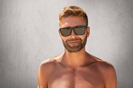 Young bodybuilder with trendy hairstyle, bristle, wearing sunglasses, standing naked over grey background. Stylish unshaven man with beautiful muscular body, isolated. People, beauty concept