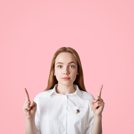 Vertical shot of blue eyed female with healthy skin, keeps fore fingers raised upwards, shows copy space for your promotional text or advertisement, isolated over pink background. Look there Stok Fotoğraf