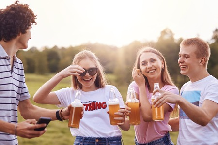 Summer time and leisure concept. Happy girls laugh at boy`s funny jokes, drink cold beverages, have cheerful expressions, spend spare time on summer field. Companionship and relationship concept Standard-Bild