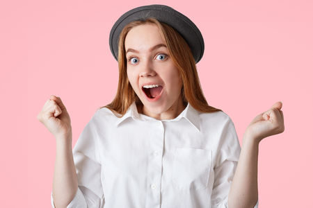 People, triumph, success and body language concept. Overjoyed elegant female clenches fists and exclaims with happiness, wears fashionable black hat and shirt, isolated over pink background.