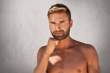 Serious man with bristle, dark attractive eyes, stylish hairdo standing topless while keeping his hand under chin isolated over grey background. Young Caucasian man with ideal musclular body Stock Photo