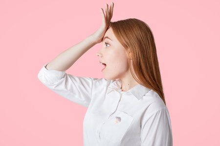 Sideways shot of beautiful female with long hair, keeps hand on forehead, regrets something, isolated over pink background. Lovely young woman in white shirt looks surprisingly into distance Фото со стока