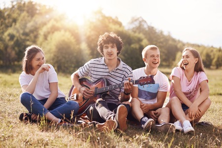 Happy female and male students enjoy picnic outdoor, sit grouped together, laugh and joke among themselves, sing songs to guitar, admire beautiful nature. People, lifestyle, amuzement concept