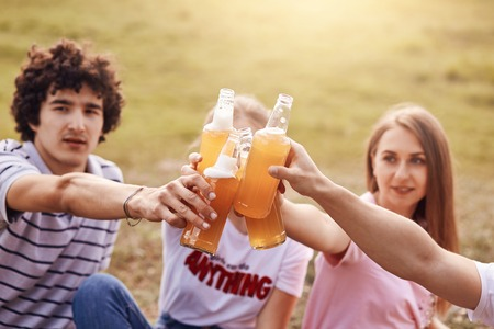 Photo of friendly teenagers spend free time in countryside on nature, clink bottles with cider, have picnic together, focus on drink. Curly male celebrates birthday outdoor with friends. Friendship Stock Photo