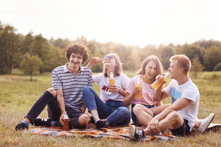 Shot of happy teenagers laugh joyfully while have picnic outdoor, drink cold energy drinks, sit crossed legs, have fun, breath fresh air, pose outside, spend weekend on nature. Young and leisure