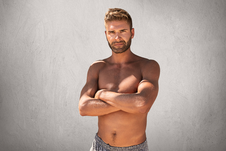 Topless handsome macho man with crossed hands, feeling his strenght and confidence posing at camera. Unshaven young guy with tanned skin and ideal sporty body isolated over grey studio background