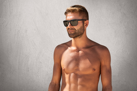 Waist up portrait of attractive macho man with bristle in trendy eyewear, standing naked against grey blank wall, looking aside with confident expression, demonstrating his suntanned, sport body