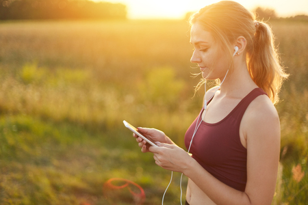 Female runner enjoying calm atmosphere while jogging on field, listening to her favourite track in earphones. Young female going in for sport. People, active lifestyle, health and fitness concept