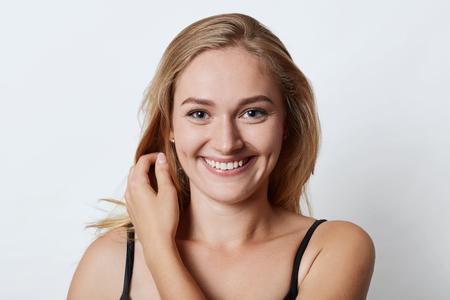 Foto de cabeza de mujer atractiva con sonrisa encantadora, ojos azules y hoyuelos en las mejillas que disfruta de las vacaciones de verano, que las va a pasar al extranjero con su novio. Concepto de belleza y emociones