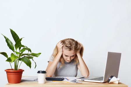 Stressful female working with figures, not knowing how to do business report, having panic, being focused on documents. Businesswoman trying to understand how to sign papers. Business concept Standard-Bild