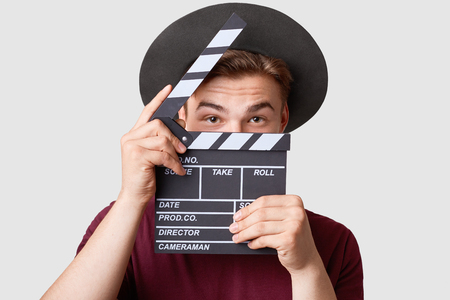 Professional male actor ready for shooting film, holds movie clapper, prepares for new scene, wears special clothes, isolated on white background. Handsome young man poses with clapboard in studio Banque d'images
